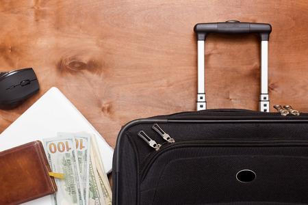 Zwarte koffer en bagage voor een zakenreis op een houten achtergrond