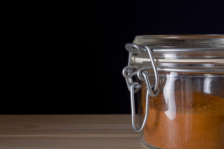 intense flavor: Ground saffron in a glass container on a wooden table on a black background