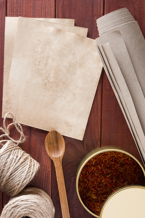 packing material: Dried saffron spice and material for packing on a wooden table Stock Photo