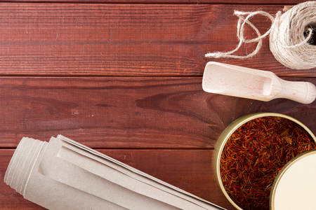 Dried saffron spice and material for packing on a wooden table Standard-Bild