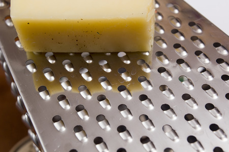 metal grater: Close up of a piece of cheese and a metal grater