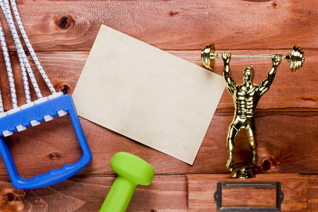 Figure weightlifter, dumbbells and expander on a wooden background