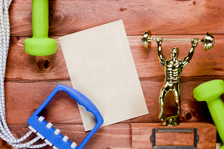 expander: Figure weightlifter, dumbbells and expander on a wooden background