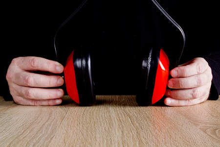 protectors: Ear protectors in human hand.  On a wooden surface. Stock Photo