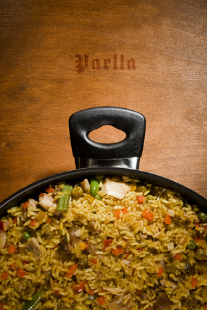 valencian: Overhead shot of a pot of chicken paella, a traditional Valencian (Spanish) rice dish made of rice, chicken, peas and capsicum.