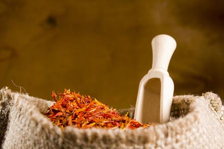 Spices saffron in a bag on a wooden background Standard-Bild