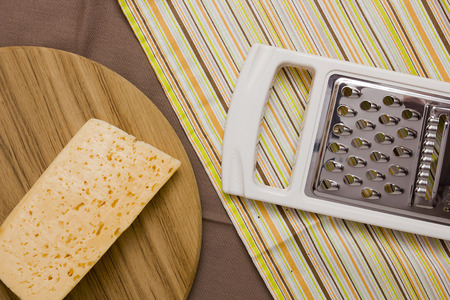 metal grater: Metal grater and cheese on a cutting board