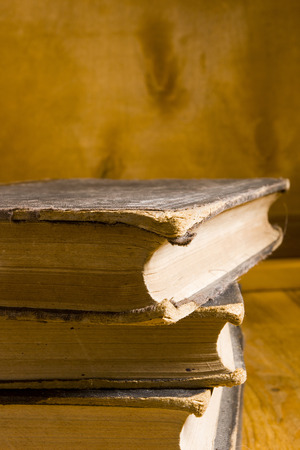 books on a wooden surface: Stack of old books in a row on wooden surface