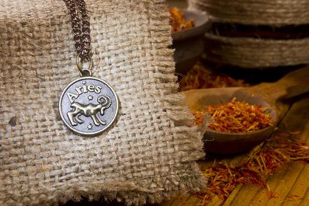 aries: Medall�n con el signo de Aries el cilicio y el azafr�n en una cuchara de madera Foto de archivo
