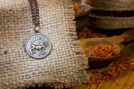 aries: Medallion with the sign of Aries on sackcloth and saffron in a wooden spoon