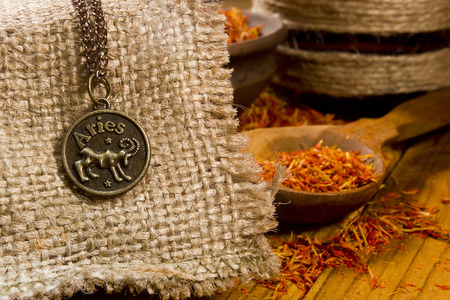 aries zodiac: Medallion with the sign of Aries on sackcloth and saffron in a wooden spoon
