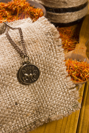 sackcloth: Medallion with the sign of Aries on sackcloth and saffron in a wooden spoon