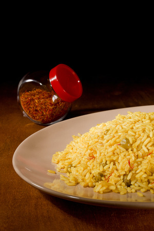 Sárga rizs sáfrány üvegedényben egy fából készült asztal