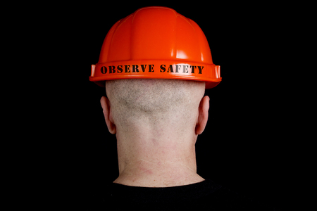 Construction worker in hard hat with an inscription observe safety on gray background Stock Photo