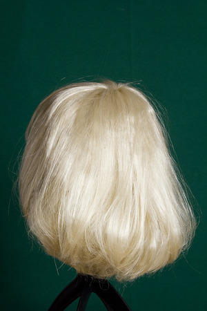 untangle: Artificial wig with white hair on a green background