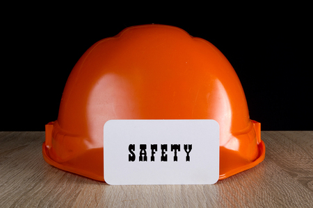 Industrial orange helmet for compliance with safety on a wooden table