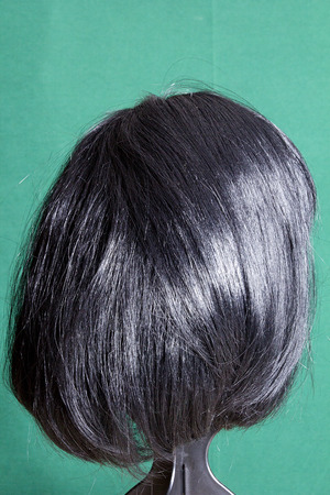 artificial hair: Artificial wig with black hair on a green background