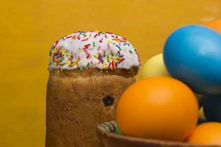 Easter eggs of different colors and cake on a wooden background Imagens