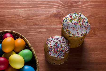 Easter eggs of different colors and cakes on a wooden background