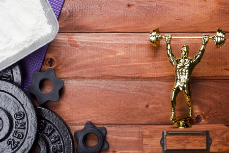 weightlifter: Figure weightlifter and dumbbells on a wooden background Stock Photo