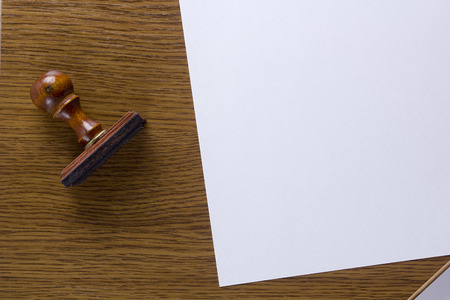 deny: Wooden stamp and a sheet of paper on a wooden table