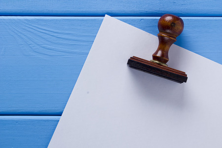 Wooden stamp and a sheet of paper on a wooden table