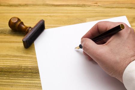 Hand met pen schrijven op een blanco papier op een houten tafel