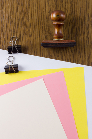 Wooden stamp and colored sheets of paper on a wooden table
