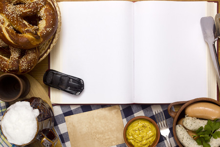 veal sausage: Sausages, pretzels, beer and a book on a wooden table