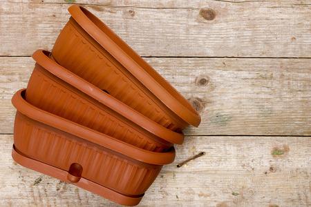 Brown plastic pots for flowers on a wooden background Reklamní fotografie