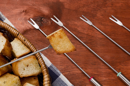 characteristic: Characteristic forks used for fondue on a wooden background Stock Photo