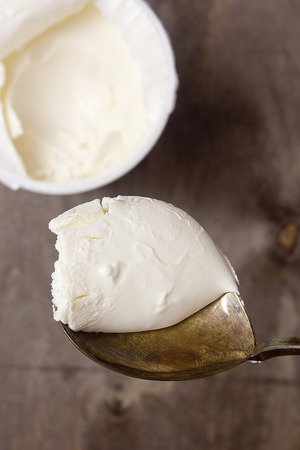 mascarpone: mascarpone cheese in an old spoon on a wooden background