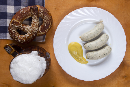 veal sausage: German pretzels and sausages on wooden background