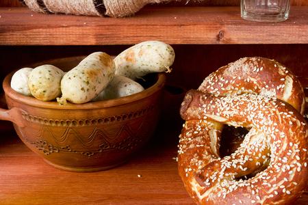 German pretzels and sausages on wooden background