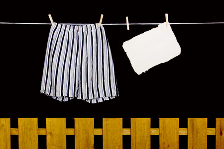dry cleaned: Mens underwear hanging on a clothesline over the fence