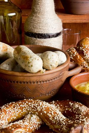 veal sausage: German pretzels and sausages on wooden background