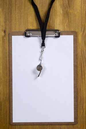 arbitrator: Whistle and paper for sports tactics on a wooden background
