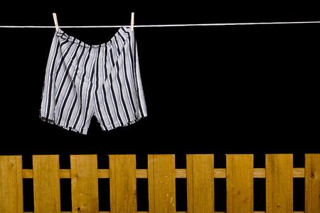 Heren ondergoed opknoping op een waslijn over de schutting