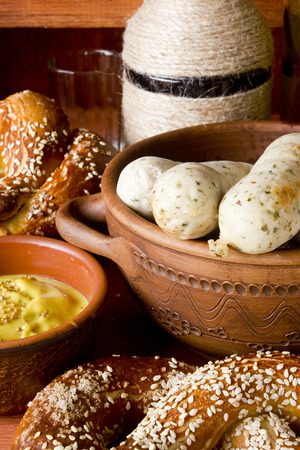 weisswurst: German pretzels and sausages on wooden background