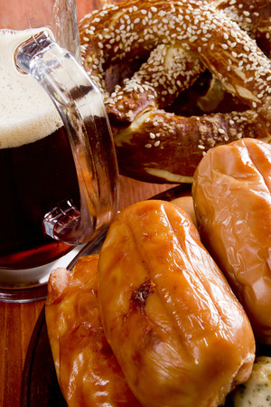 veal sausage: Traditional sausages, pretzels and beer on a wooden background Stock Photo