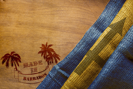 stamping: Hot stamping on a wooden surface - Made in Barbados. Barbados flag State. Stock Photo