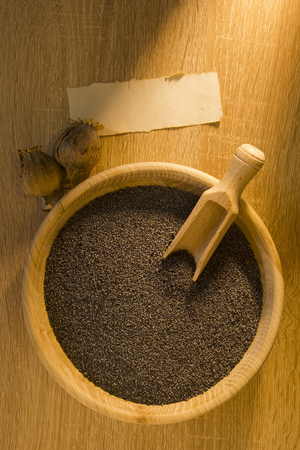 poppy seeds: Poppy seeds in a wooden bowl on a wooden background
