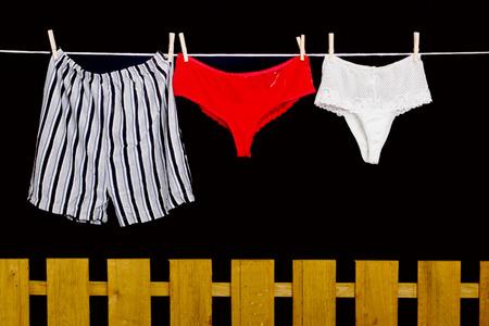 man underwear: Woman panties and man underwear on clothesline on black background Stock Photo