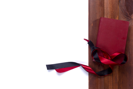 black satin: Black red satin ribbon and a book on a wooden background