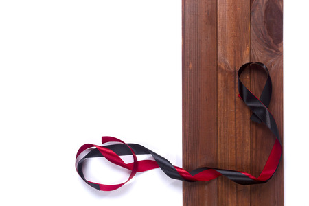 Black and red satin ribbon on the wooden background