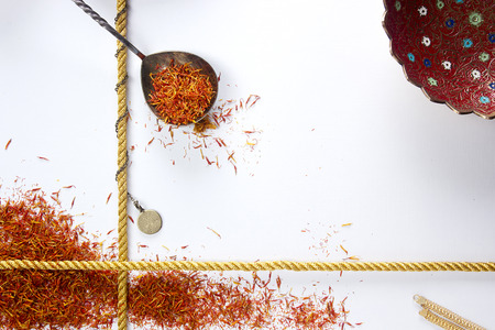 Saffron in a metal spoon on a white background