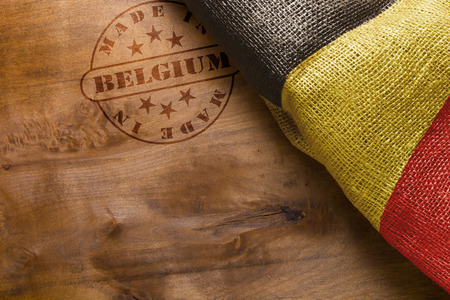 postmark: Hot stamp imprint on a wooden surface - Made in Belgium. Belgium flag.