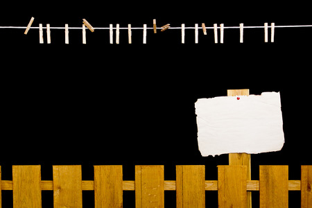 Wooden fence and rope for drying clothes on a black background