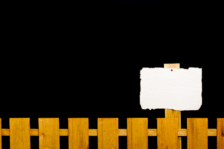Wooden fence with a paper plate against a black background