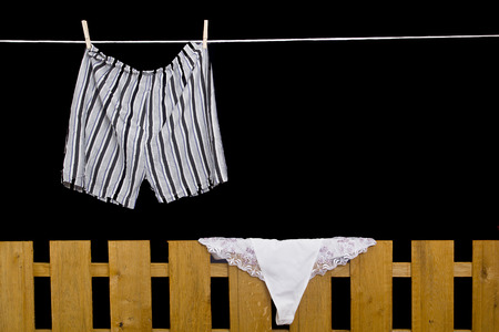 dry cleaned: Mens and womens underwear hanging on the rope and on the fence